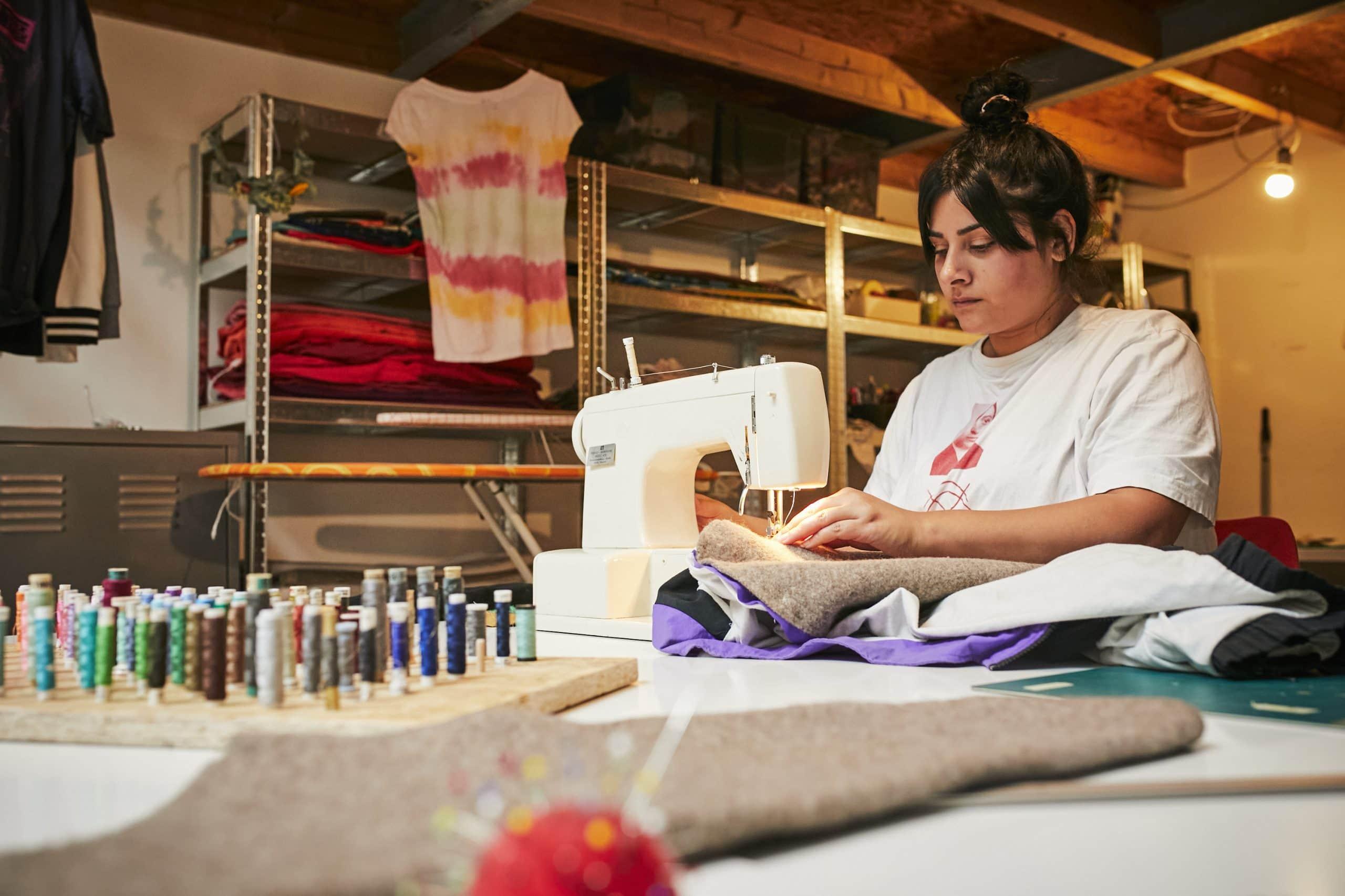 Frau remixt Kleidungsstücke an Nähmaschine